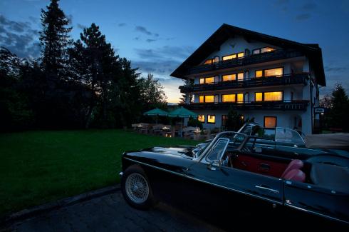 Haus bei Dämmerung mit Oldtimern - Hotel Konradshof