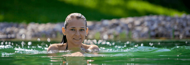 Dame beim Bad im Naturschwimmteich - Hotel Konradshof
