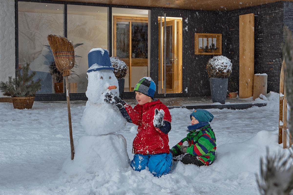 Vor dem Eingang im Schnee spielende Kinder - Hotel Konradshof