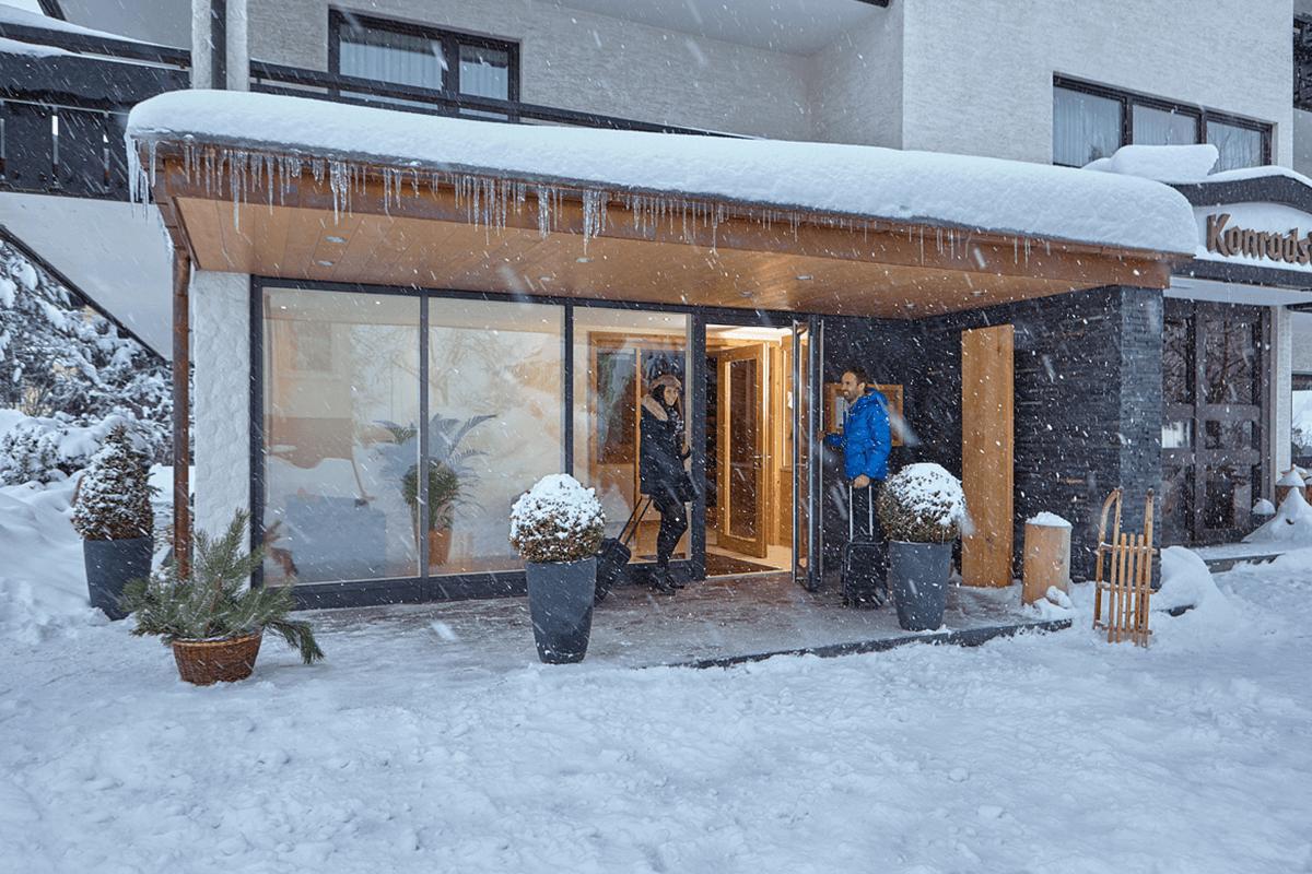 Hoteleingang mit Gästen im Schneegestöber - Hotel Konradshof