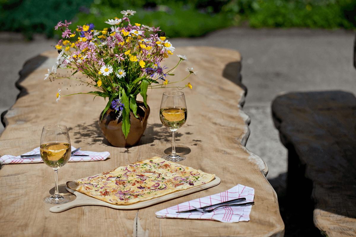 Flammenkuchen mit Weingläsern auf Holztisch - Hotel Konradshof