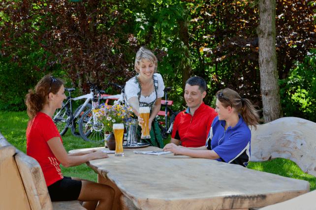 Dame serviert Bier für Radsportler - Hotel Konradshof