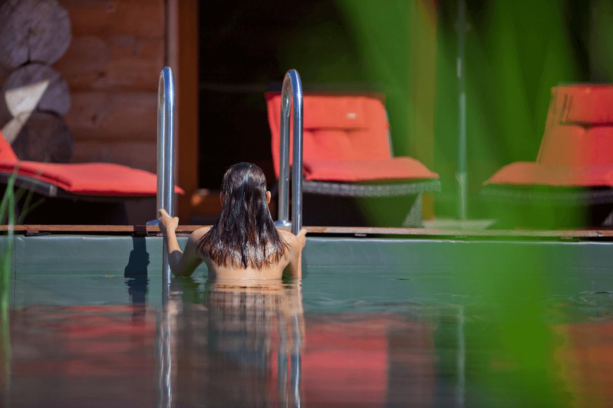 Frau steigt aus Naturschwimmteich aus - Hotel Konradshof