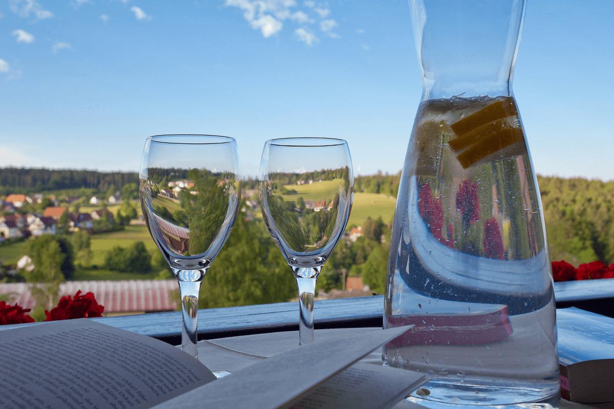 Wasserkaraffe mit Gläsern vor Landschaft - Hotel Konradshof