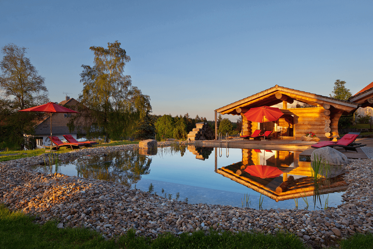 Naturschwimmteich mit Blockhaushütte im Sonnenuntergang - Hotel Konradshof