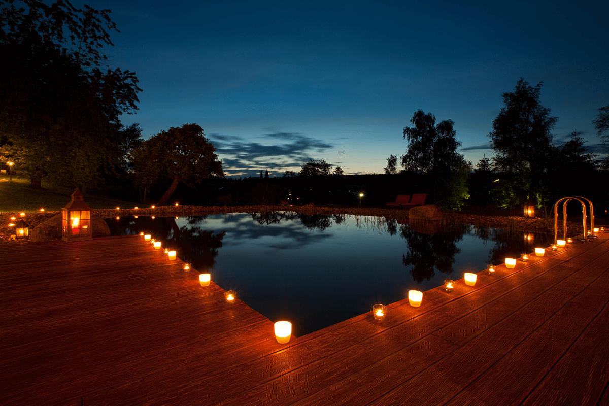 Naturschwimmteich bei Nacht mit Kerzenlicht - Hotel Konradshof